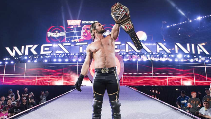 WWE' Seth Rollins holds up a title belt on the entrance ramp at Wrestlemania.
