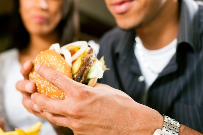 A man takes a bite of a cheeseburger.