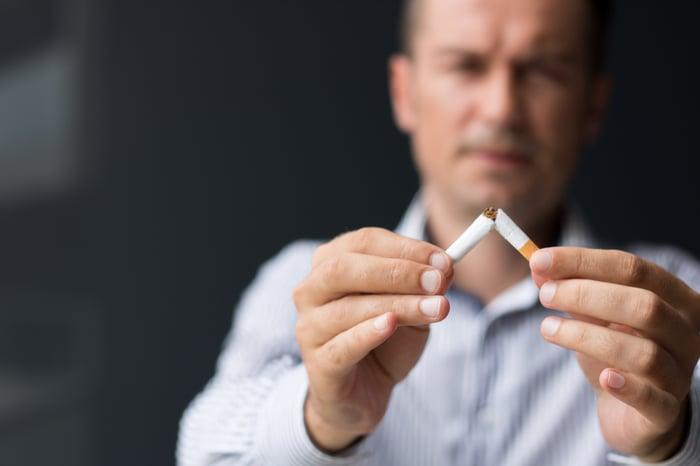A man breaks a cigarette in half