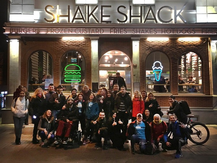 Shake Shack store with about two dozen people standing or sitting outside it.