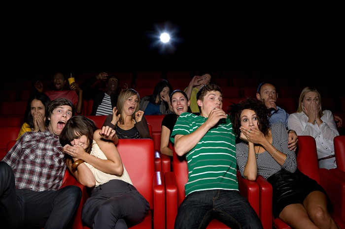 A movie theater full of people reacts to something scary or shocking on the unseen screen.