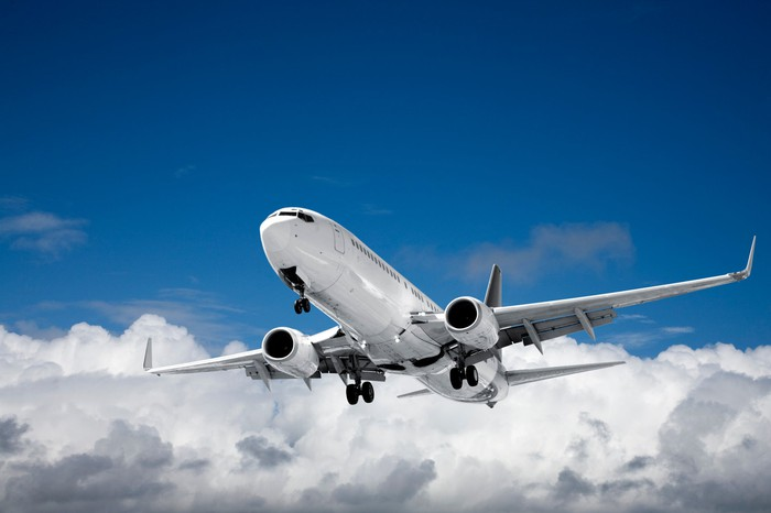 An airplane in flight with blue sky and white clouds in the background
