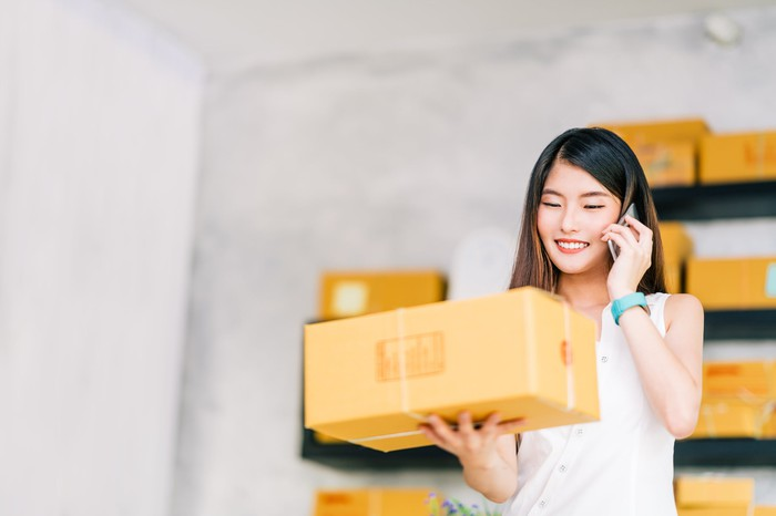A young woman holds a delivery box in one hand and speaks on her cellphone.