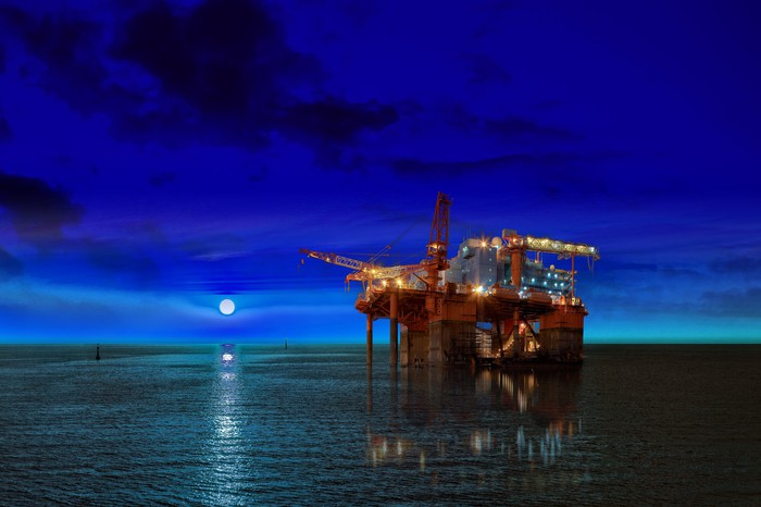 An offshore oil platform at night.