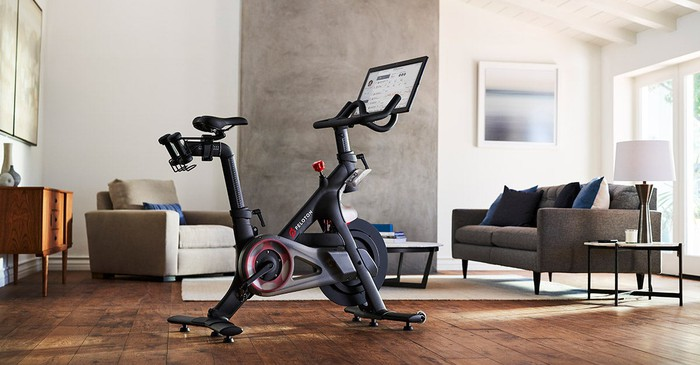A Peloton bike featuring a big video screen attached to the top, in a living room.