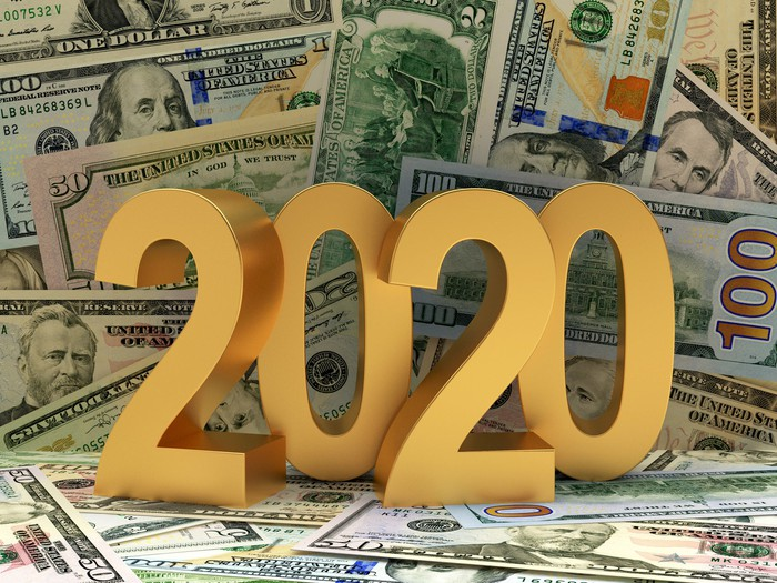 Large gold numbers spelling out 2020 atop a messy pile of assorted cash bills.