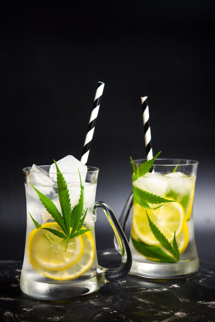 Two lemonade beverages with marijuana leaves displayed inside them