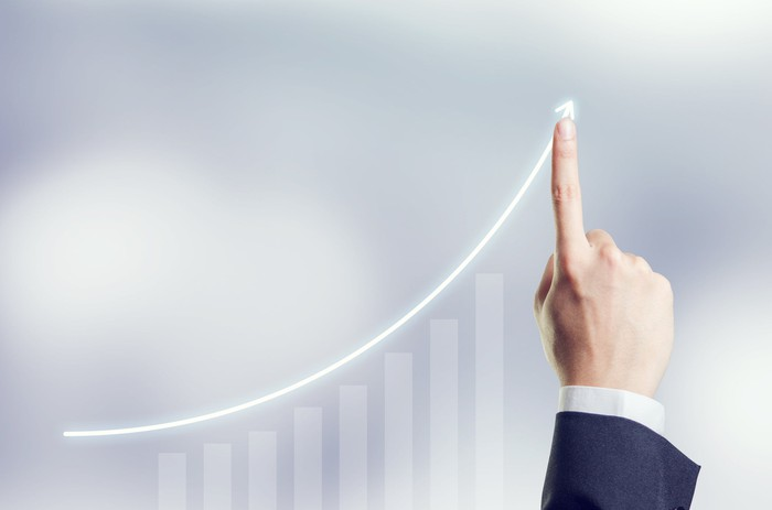 Businessman's index finger pointing to a line chart sloping upward.