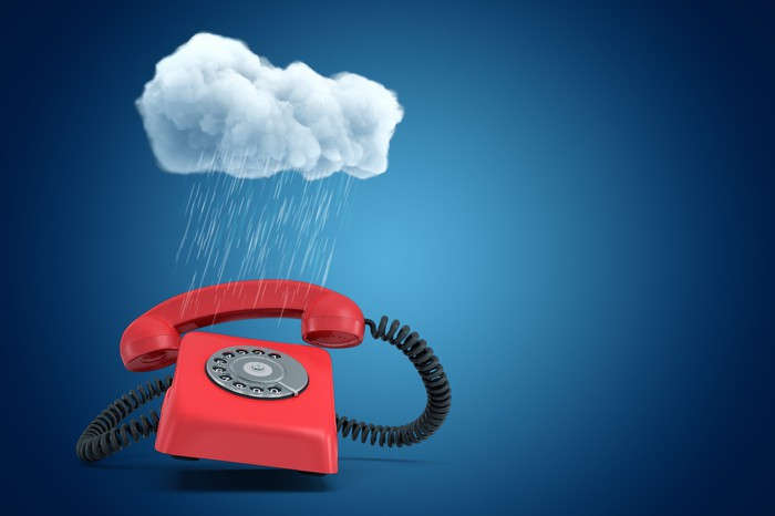 Digital rendering of a red rotary phone under a small cloud that's dropping torrential rain on it.