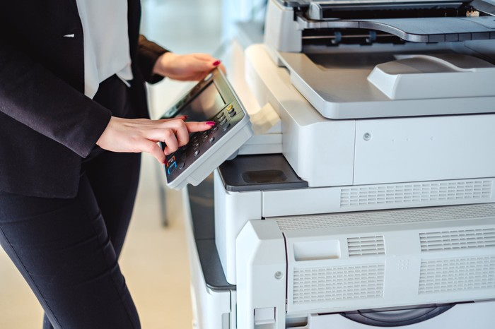 Person at copier touching the control screen.