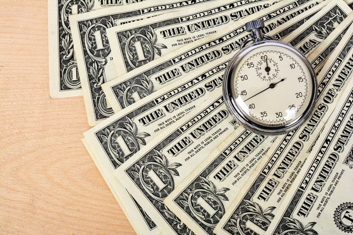 Dollar bills with a stopwatch on top of them.