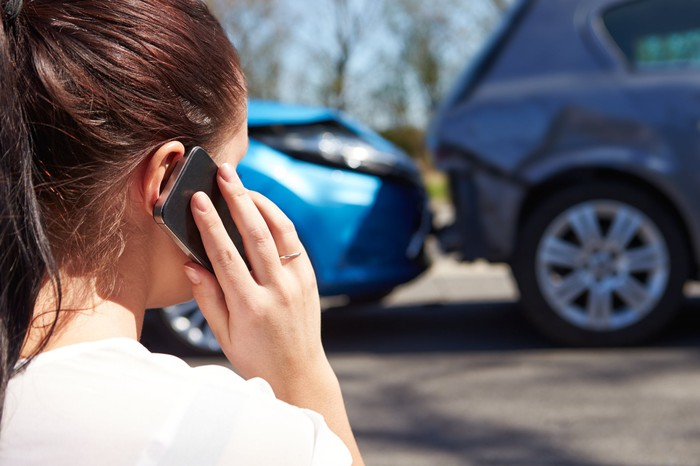 A woman making a call on her smartphone while standing in front of two cars involved in an accident.