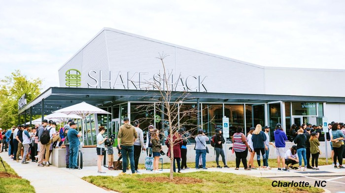 People standing in line outside a Shake Shack restaurant.