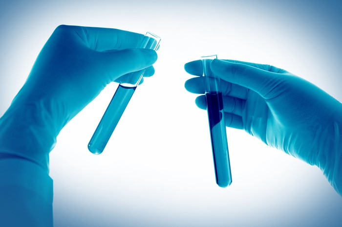 Gloved hands holding two test tubes.