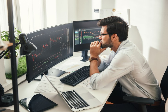 A young trader with glasses mulls over stock prices on his desktop monitors.