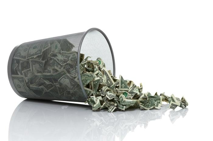 Crumpled paper dollar bills spilling from an overturned wastebasket