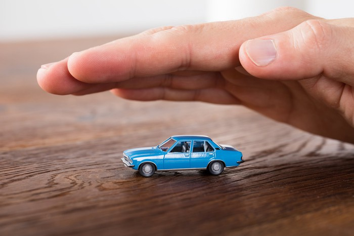 Hand hovering over a toy car.