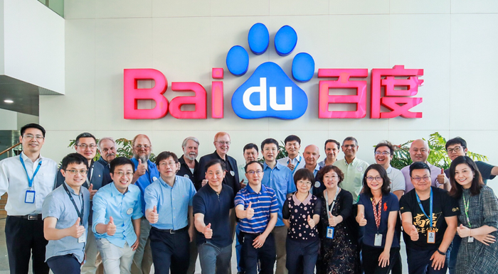 About two dozen Baidu researchers posing in front of the corporate office logo.
