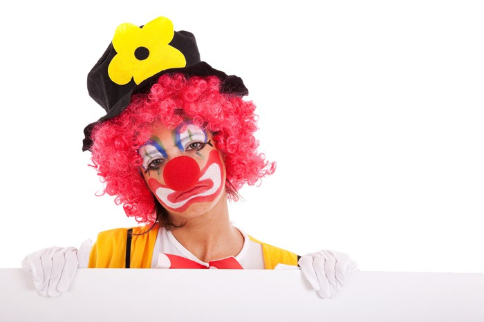 Sad clown standing behind a white wall.