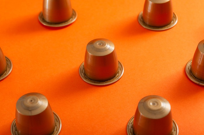 Bronze-colored coffee pods turned upside down on an orange surface.