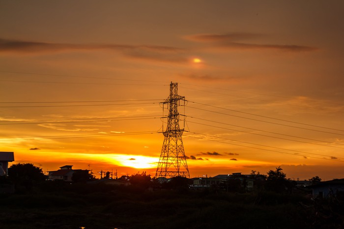 A power transmission tower in front of a sunset.