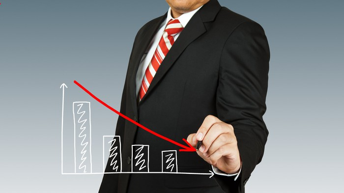 Man in suit drawing a downward sloping chart.