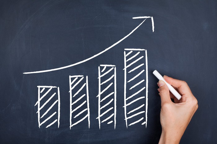 A chalkboard sketch of a bar chart with an arrow highlighting a growth trend.