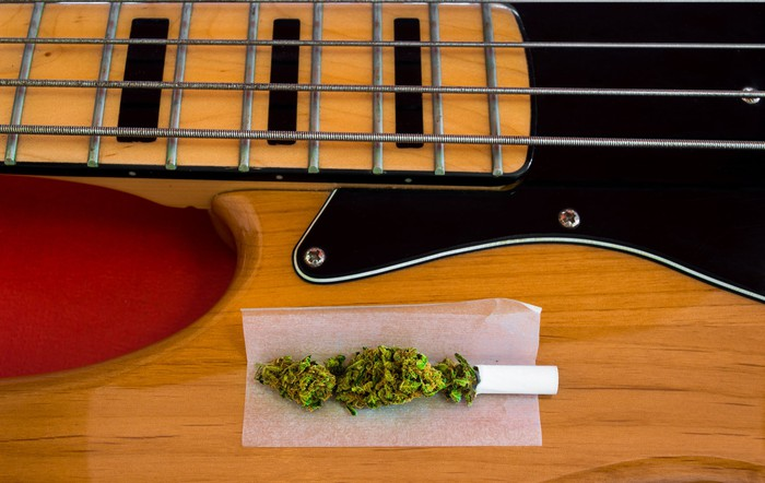 An unrolled marijuana cigarette on top of a bass guitar.