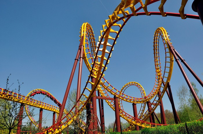 Close-up shot of an intricate roller coaster, showing lots of twists and loops in red and yellow steel tubing against a clear blue sky.