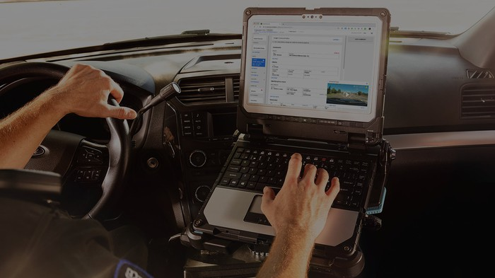 Police officer entering data into in-car computer system