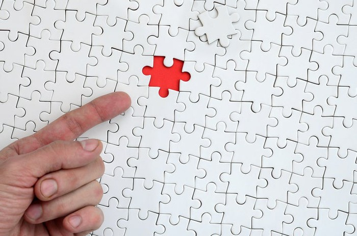 A finger points to a missing puzzle piece in a large jigsaw puzzle.