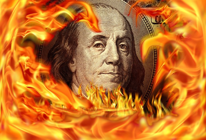 A hundred dollar bill surrounded by flames, with only Ben Franklin's face in the center that's still fire free.
