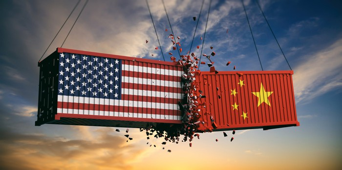 Two shipping containers smashing together, one with an American flag and the other with a Chinese flag.
