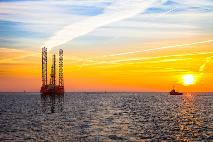An offshore drilling rig with the sun setting in the background