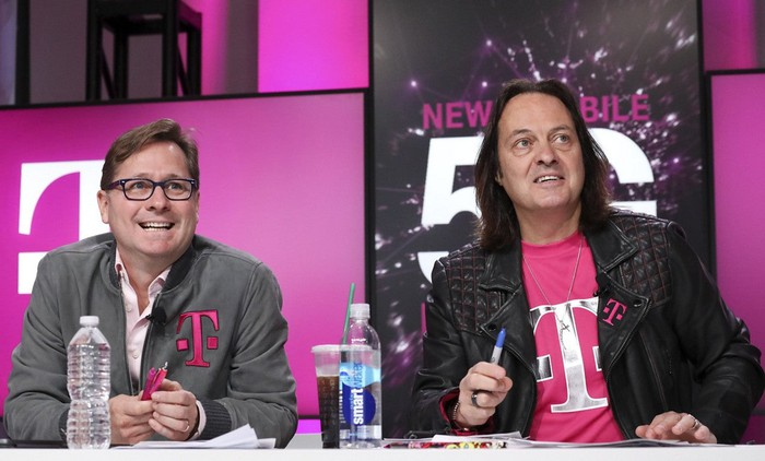 T-Mobile President Mike Sievert and CEO John Legere sitting at a table with T-Mobile branding behind them