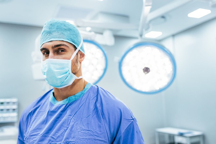 Surgeon with mask on standing in room