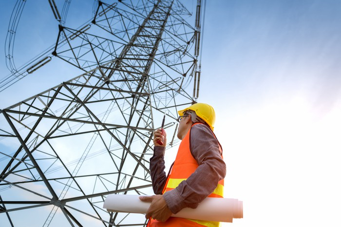 A telecom tower and a construction worker looking up at it
