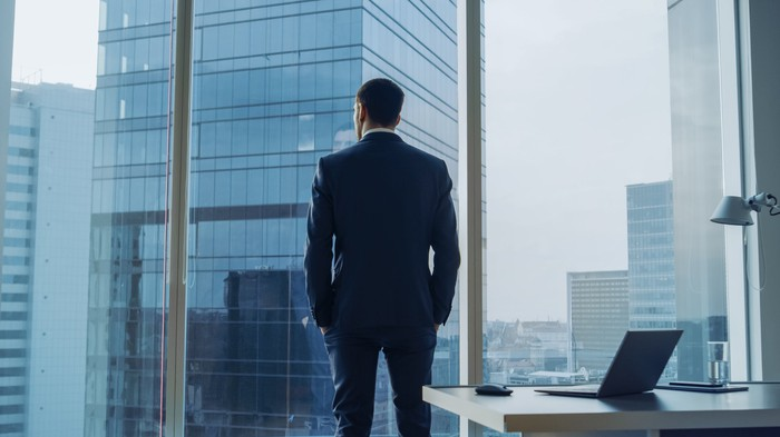 A businessman staring out of an office window.