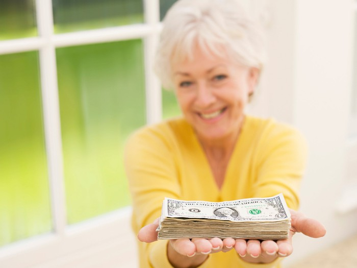 A smiling senior woman holding a neat stack of cash in her outstretched, cupped hands.