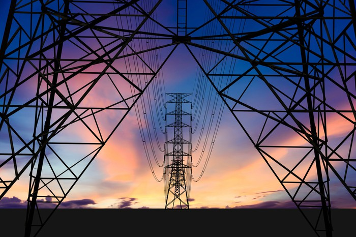 Low-angle photograph of two high-voltage towers and power lines in perspective against a colorful sunset.