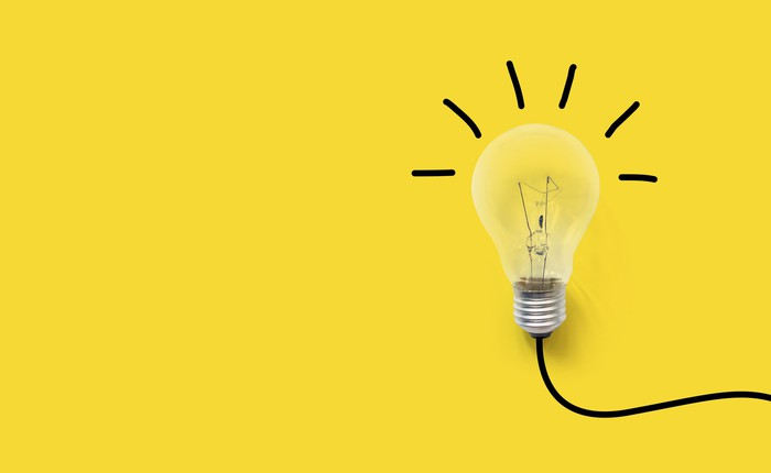 Light bulb on a yellow background with a black wire emitting black lines.