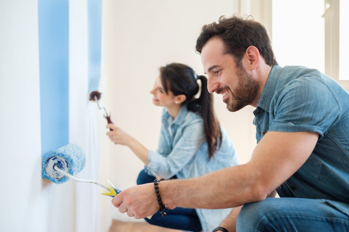 A man and a woman roll blue paint onto a wall.