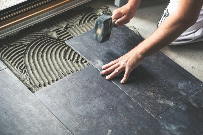 A man installs tiles on a floor.