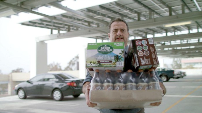 Man carrying cases of soda and coffee