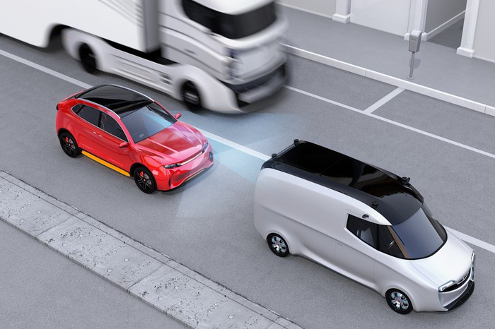 Rendering of a red car sensing an impending collision with a white van, which triggers an emergency braking action.