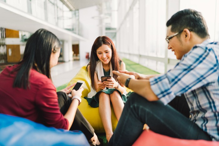 Three smiling Asian youngsters gathered in a public meeting space, all focusing on their smartphones.