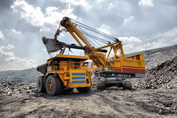 An excavator dumping material into a mining dump truck in an open-pit mine.