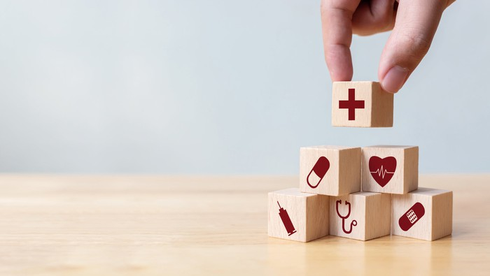 Wooden blocks with various healthcare symbols printed on them being stacked into a pyramid on a wooden table.