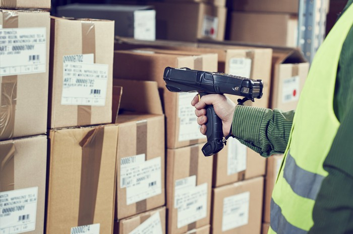 A warehouse worker uses a handheld device to scan bar codes on a large number of stacked cardboard boxes.