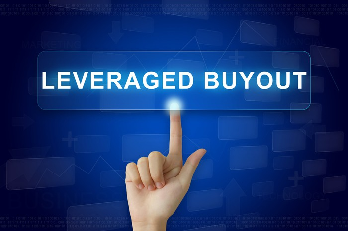 Index finger pointing to a blue panel displaying the words Leveraged Buyout.